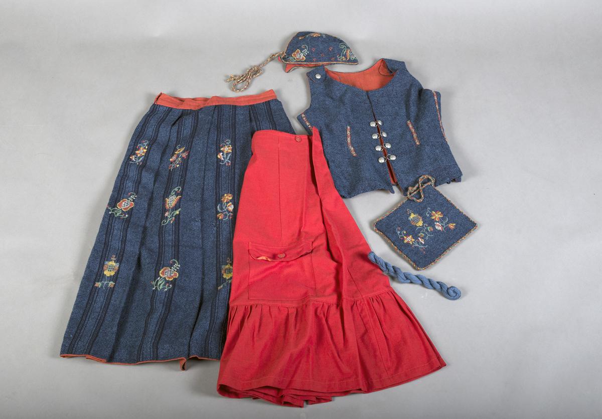 Rødt underskjørt med kappe og lomme, brodert linskjorte, brodert ull-skjørt, brodert ull-vest, brodert lue, brodert veske og blått brodérgarn i ull.