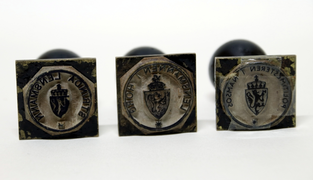 Tre metallstempler med sort trehåndtak. Et av stemplene er teipet grunnet løs del.