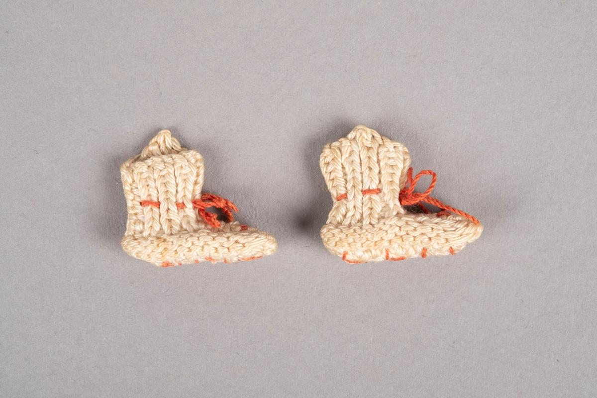 """Ett par strikkede miniatyrsokker. Sokkene er strikket med hvitt garn. De har rosa snøring. Det er brodert """"Grini"""" på den ene sokken og """"1944"""" på den andre."""