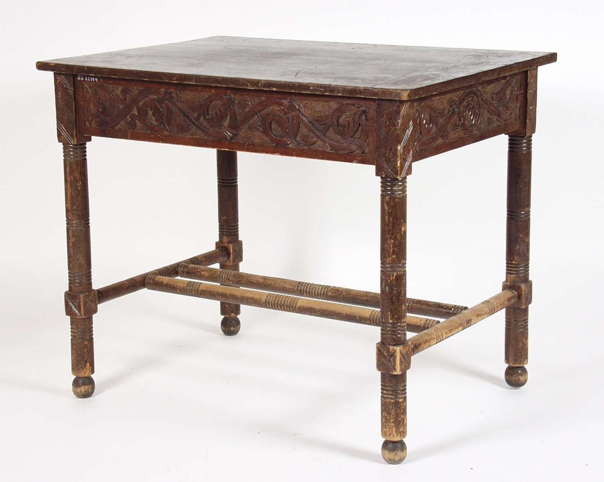 Brunmalt bord med dreide ben og sprosser, med treskurd med bladmotiv på sarg.