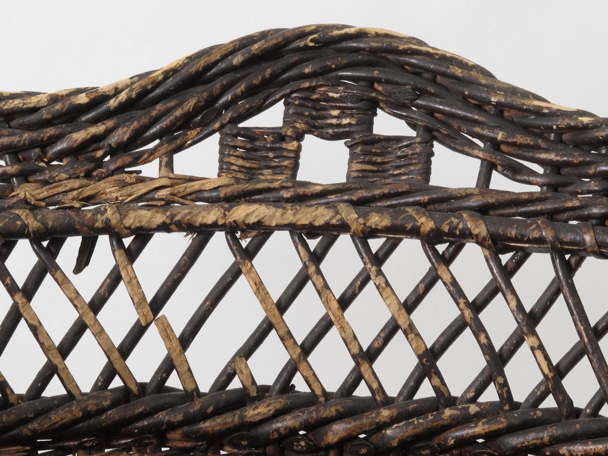 Sortmalte kurver, den ene med korstingsbånd om korpus,  sydd med ullgarn på strie, i rødt, brunt, grønt med ullsnor på hver side. Rett bakside, rundet forside, skrå sokkel, tunget øvre kontur.