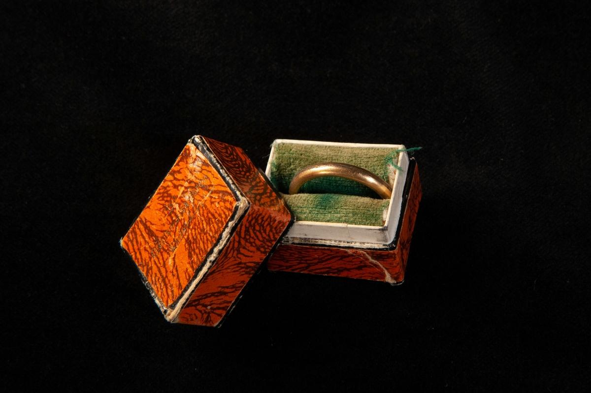 """En ring i gulddoublé. Ligger i en rödklädd pappask, invändigt klädd med grön sammet. På undersidan av asken står """"Min mammas ringar""""."""