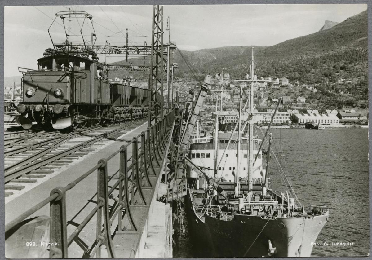 """Malmhamnen i Narvik med """"M/S Karmas"""" vid kaj. På bron syns ett ellok med malmvagnar. Luossavaara-Kiirunavaara Aktiebolag, LKAB F 29.  Statens Järnvägar, SJ Ub med malmtåg."""