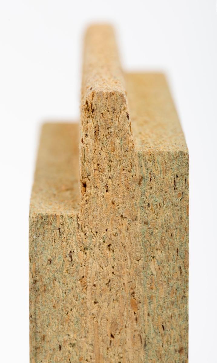 En rektangulær sponplate, vareprøve, på 12 cm x 8,9 cm x 2,5 cm. På vareprøvas ene side er det en utstikkende profil, fjær (fjør), som settes sammen, bankes inn, i den andre platas not (utfrest spor, fordypning).  Påklistret etikett på vareprøvas ene side har denne teksten: NY SPESIAL FOR VÅT - ROM HUNTOSPON NORSK WALLBOARD AS 3-sjikts sponplate for bygnings-, møbel-, trevare- og skipsindustrien.  Huntospon er spesielt egnet til allslags innredningsarbeid og modernisering av hus og leiligheter. Videre i møbelindusttien til fresmstilling av skap, benker, dører etc., og i trevareindustrien til veggfaste seksjoner, benker etc. Huntospon har stor styrke og god spikerfastehet. [På etiketten er det også en tabell som gjengir ulike platetykkelser, kantbearbeiding, formater og vekt i kg per kvadratmeter. Tabellen er ikke gjengitt i registreringen.]