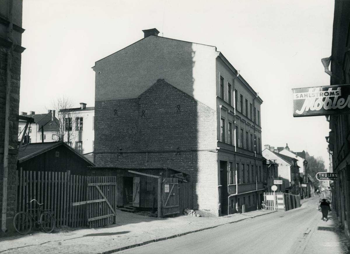 Gatuvy från Tunnbindaregatan i Norrköping. Byggnaden i bild ligger i kvarteret Haken (nr 8), på Tunnbindaregatan 21. Bilden är tagen i samband med rivningsansökan 1956. Vy mot Nordväst.