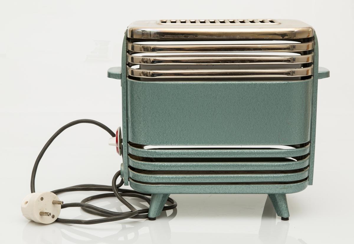 Blågrønn og sølvfarget emaljert stråleovn. Rektangulær med avrundede hjørner. Toppen er eloksert og har luftespalter. Det er også luftespalter i ovnens underdel. To håndtak på kortsidene. Bryter for varmeregulering på den ene kortsiden. Effekten kan reguleres på 250, 500 og 1000.