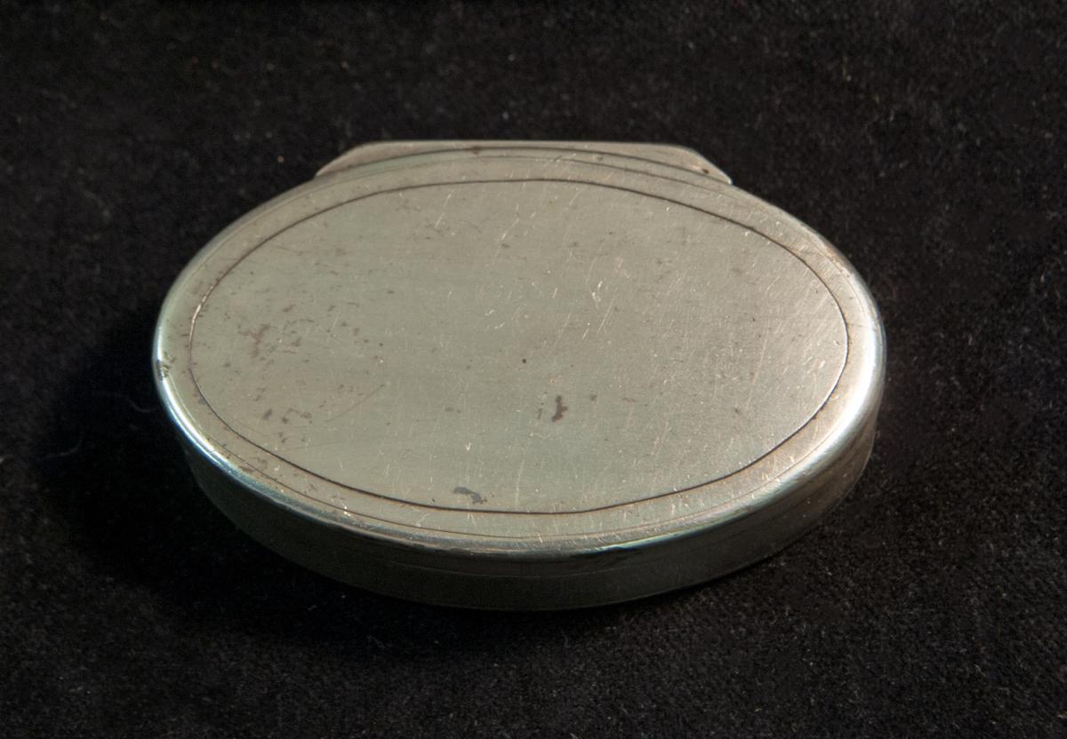 """En oval dosa av silver. Slät modell med randdekor. I botten graverade ägarinitialer i spegelmonogram: """"JH """".Invändigt förgylld. Stämplad invändigt i botten."""