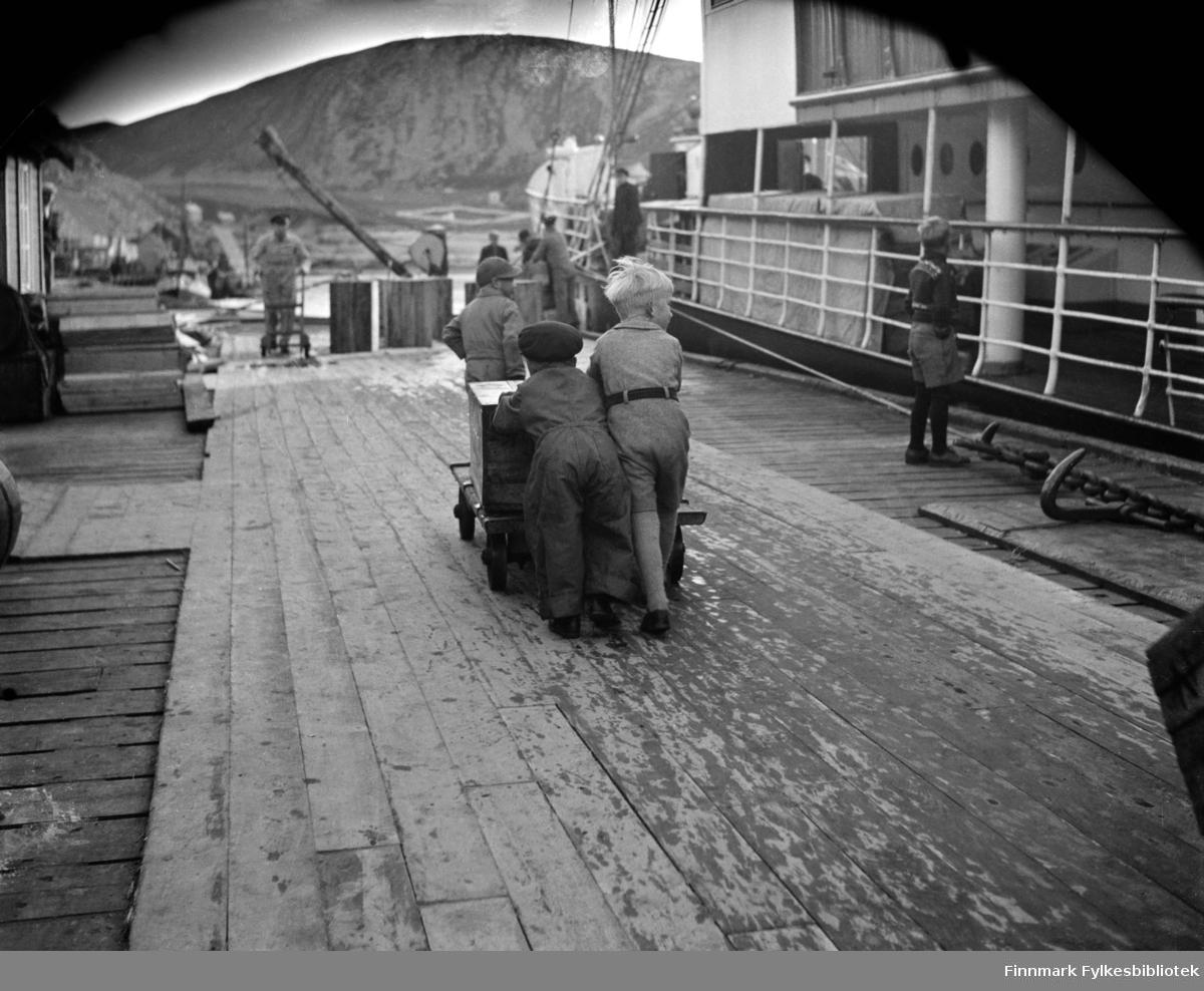 Kjøllefjord 1940. Sverre Evensen styrer tralla med kasser med saltfisk og vennene Hans Fredrik Horst og Jon Svendsen går bak og dytter. Hans Fredrik i arbeidstøy og Jon Svendsen pent kledd i kortbukser. Han var eneste gutten i familien og ble godt tatt vare på, ifølge Svendsen selv. Til høyre ligger hurtigruta, muligens er dette DS Prinsesse Ragnhild som skimtes i bakgrunnen. Hurtigruta Prinsesse Ragnhild er fotografert på flere bilder i denne serien. Kassene var merket NF som står for Nils Foldal.    Nils Foldal kom fra Follestaddalen ved Ørsta. Han kom til Kjøllefjord i 1912 og fikk arbeide hos brødrene Aarsether som den gang disponerte Horst & Christensenbruket. I 1914 kjøpte han en eiendom av Sveen der det var noe bebyggelse. Han startet med kjøp av fisk, bl.a. sild samt tranproduksjon, restaurerte bygninger og forlenget kaia, og i 1927 overtok han som dampskipsekspeditør for Vesteraalens Dampskibsselskab som hadde tre hurtigruter og flere godsbåter i Kjøllefjord. Foldal-familien flyttet fra Kjøllefjord til Ålesund i 1932.   Utdrag fra tekst hvor Foldalbruket forteller om Nils Foldals virksomhet:   «Foldalbruket ble bygget opp igjen etter krigen. Frem til 1959 hadde Foldalbruket også eksepdisjonskai med hurtigruteanløp. Foldalbruket var tidligere et fiskebruk med tradisjoner tilbake til 1900-tallet. Sunnmøringen Nils Andreas Foldal ankom Kjøllefjord i 1917 og fikk jobb ved Aarsæthers trandamperi. Her lærte han tranproduksjon og tørrfiskproduksjon og etablerte så fiskebruket Foldalbruket i 1917 og de drev helårsdrift. Det ble kjøpt fisk til både salting og tørking. Kassene med saltfisk på bildet er sannsynligvis iferd med å bli lastet om bord. Den største fisken ble flekket og saltet før den ble sendt til Sunnmørskysten og tørket som klippfisk. Resten ble sperret og tørket. Denne tørrfisken ble eksportert til både Italia og Afrika. Nils Foldal ble ekspeditør for Vesteraalens Dampskibsselskap i 1926, og bygget i denne sammenheng ut kaia ved bruket slik at båtene k