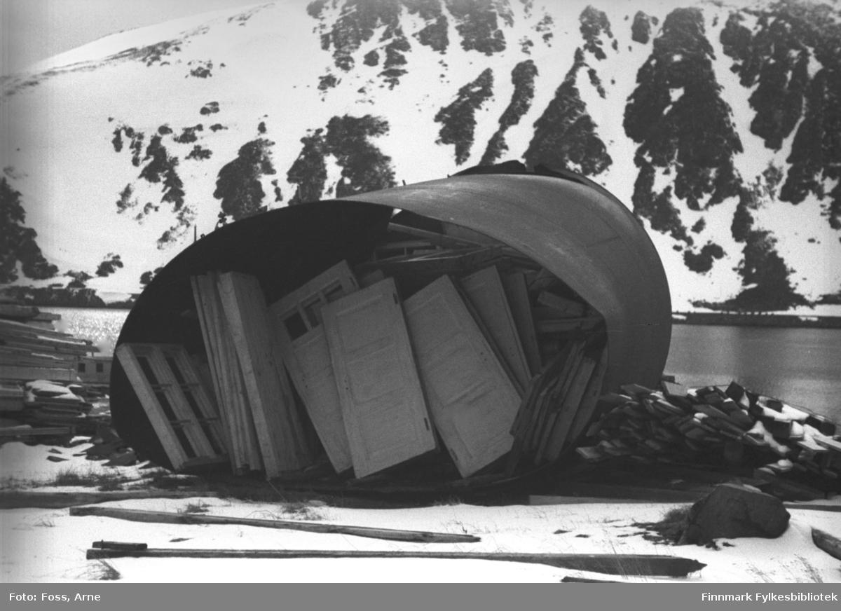 """Honningsvåg, mai 1946. Dører og vinduer er lagret under en """"presenning"""" mot vind og vær. Det var utfordrende å lagre materialer og utstyr. Trelasten ble ofte, spesielt i begynnelsen av gjenreisningsarbeid, dårlig stablet, vindskjev og rå og vanskelig å håndtere. Utover vinteren i 1945-1946 begynte det å bedre seg."""
