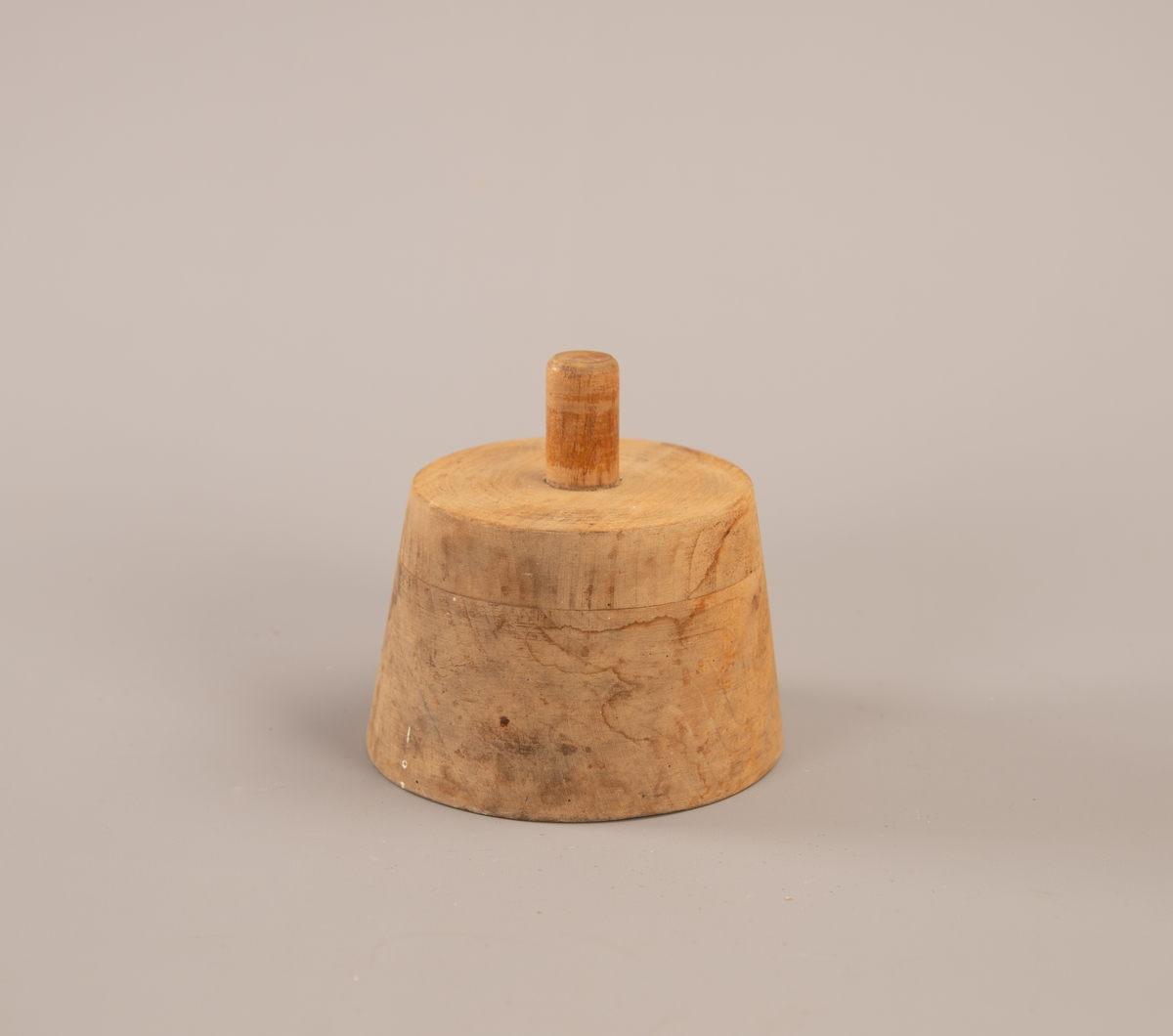 Kjegleformet hatteform med håndtak i tre på toppen. Håndtaket er limt inni et hull som er boret inn i trestykket.