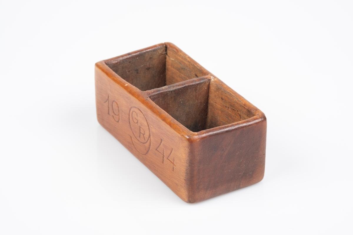 En liten beholder med to rom. Det er inngravert initialer på den ene siden og årstall med Grinisymbol på den andre siden.