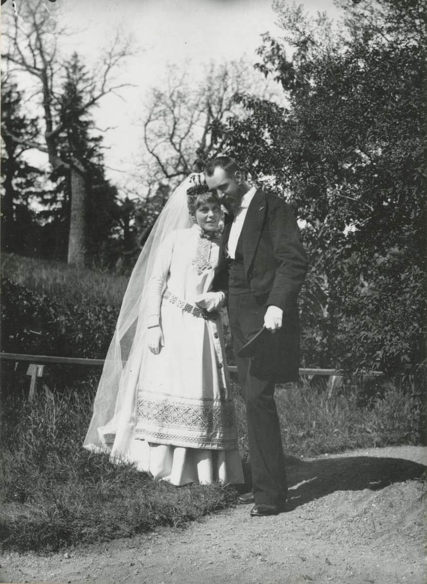 Bröllopsporträtt i helfigur föreställande konstnären Julius Kronberg och hans hustru Ellen (född Scholander). Bruden är iklädd reformdräkt av vitt ylle med blå broderier ritad av konstnären. Det är brudens bror Sven Scholander som tagit bilden.
