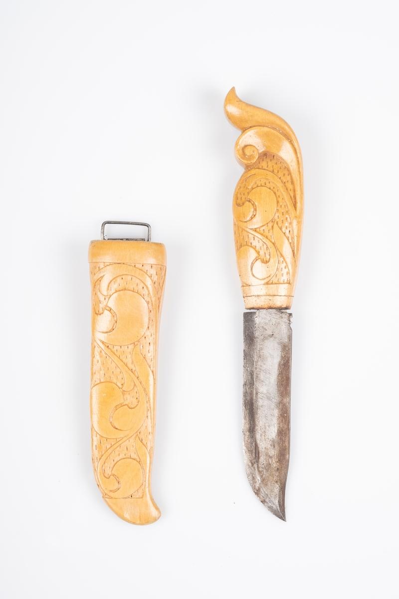 Tollekniv med slire og skaft i tre og knivblad i jern. Det er utskåret akantusmønster på skaftet og sliren. Det er inngravert akantusmønster på knivbladet. Det er opphengskrok festet til baksiden av sliren.