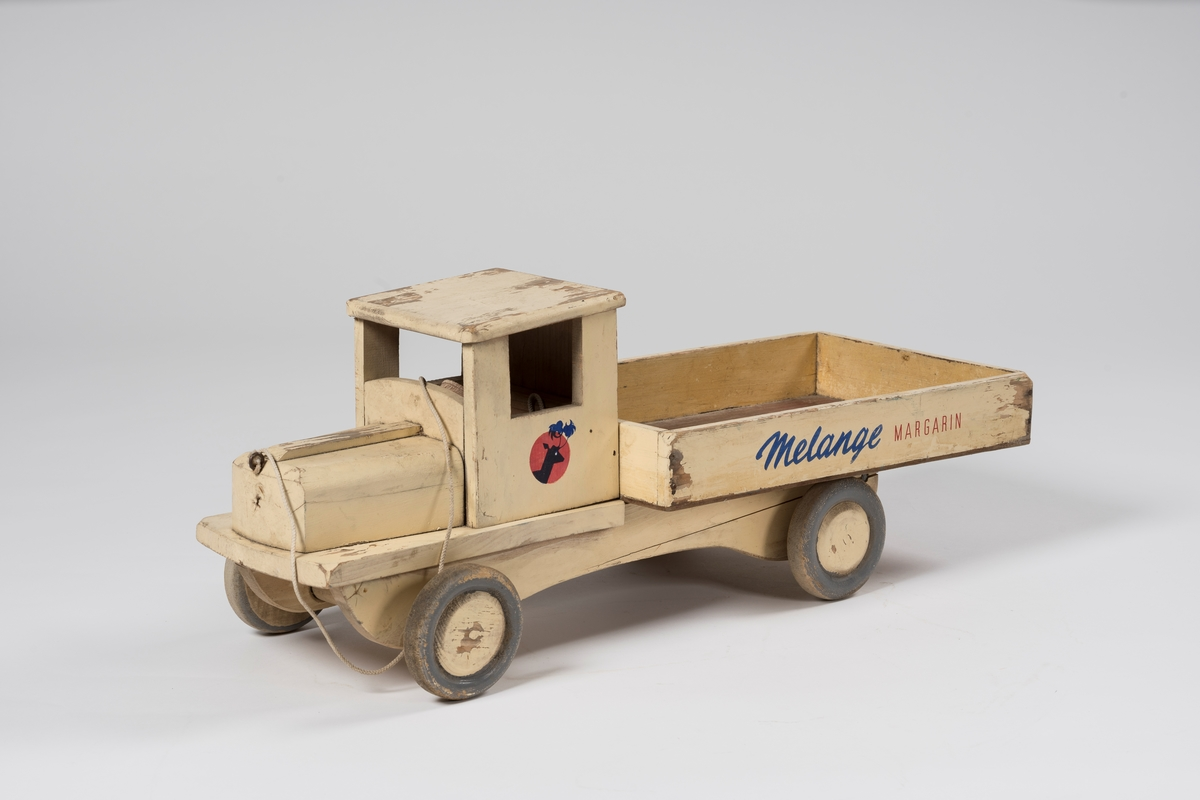 Form: Gammeldags utseende lastebil med stort og bredt lasteplan med lave karmer.