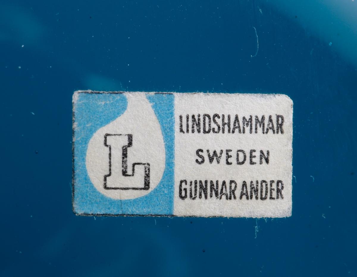 """Spargris. Kupan (kroppen) päronformad. Kort hals, rak krage (nosen). Rektangulär etikett med ett """"L"""" inom en bubbla på blå botten samt text.  Inskrivet i huvudkatalogen 1964."""