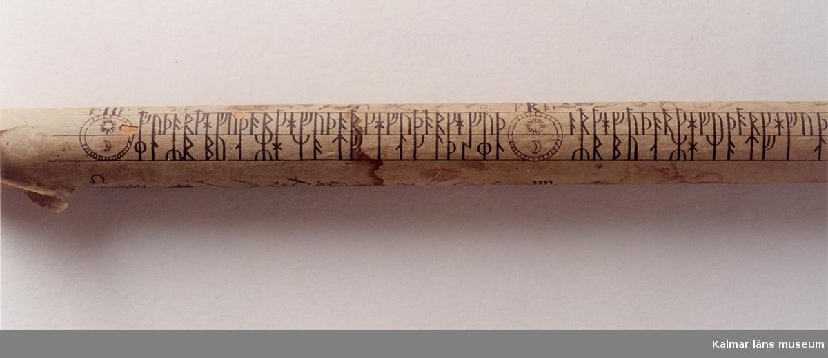 KLM 1653. Runstav. Trind stav överdragen med vitt papper, varå runor och figurer är tryckta i svart.