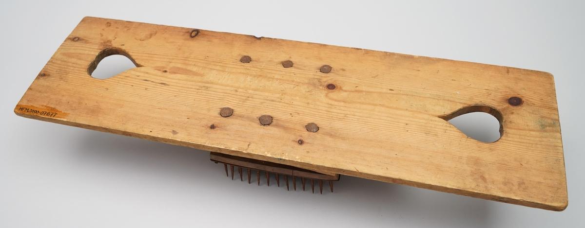 Hekle. Rektangelforma jarn plate med spisse jarnpiggar (12 x 10 stk) spikra til ei treplate i same storleik. Denne plata er spikra vidare ned i treklossar på kvar langside, slik at det e luft under. Treklossane er feste med tre jarnspikrar (slått inn frå undersida) med store hovud til ei trefjøl. Trefjøla har eit hjarteforma hol i kvar ende, og det er rissa inn strekar som dekor. Langsidane er profilerte heile vegen. Piggane sit tett.