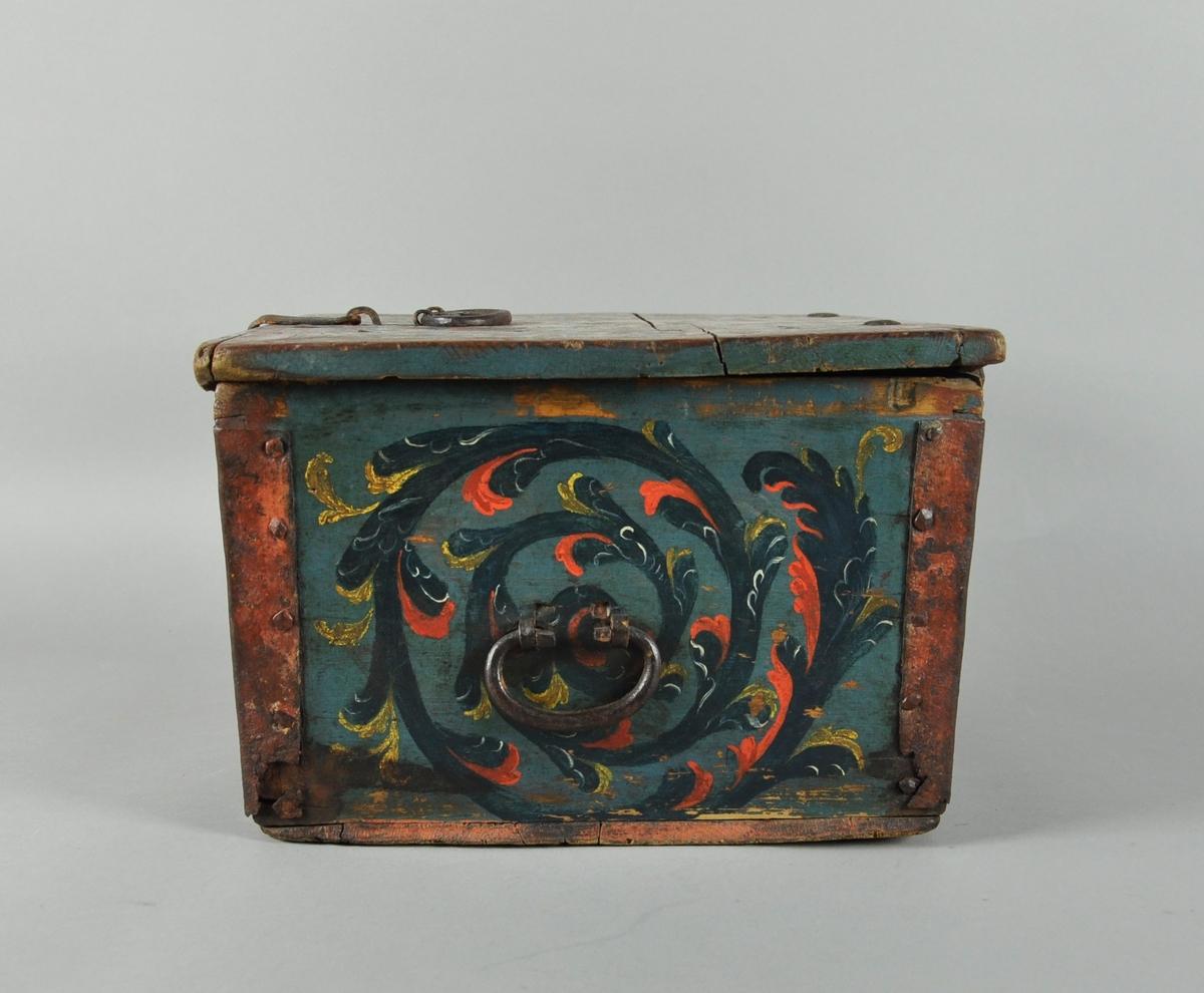 Rosemalt ferdaskrin med jernhank på lokket. Lås på lokket som kan festes på skrinet. Nøkkelbeslag på forsiden.