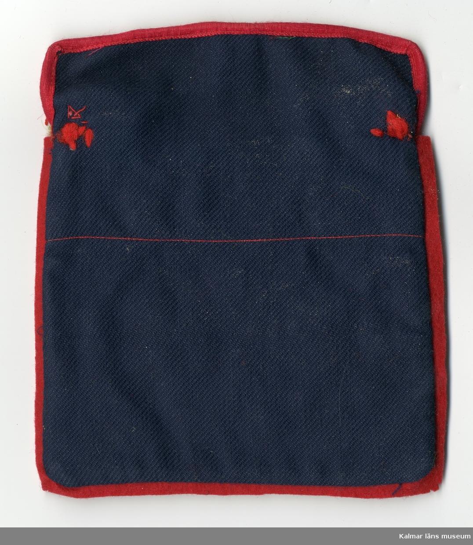 KLM 28082:411 Ficka, kjolväska, kjolsäck eller kjolficka av textil, ylle och bomull. Ficka, baksida blå, framsidan av linne, vit, rikt med garneringar i filt, rött, grönt och gult. Framsida, upptill sicksackklippt bård, röd med flätstygn i grönt. Nertill garneringar i filt i stilistiska mönster av hjärtan, blommor och sydda vita flätsöm. Ovanför ficka framtill, två ylletofsar i rött och grönt, samt synligt foder, röd botten med motiv av blomster. Foder, inuti, delvis av bomull, vit. Kant med passepoalsöm. Tillbehör till nationaldräkt. Inuti kjolfickan ligger tre prickar, av filt, två gula och en grön.