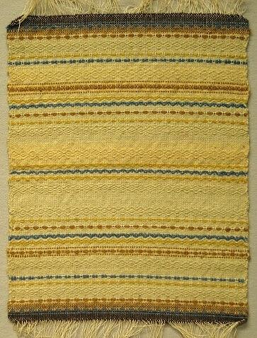 Dukprov med  fransVarp: lingarnInslag: ullgarn i naturvitt, blått, brunt och gultUnder 2:a världskriget (kristid) fick industrifärgat garn endast användas till nyttovävar. Därför vävdes det mycket med ofärgat och växtfärgat garn.Hos väverskorna var det populärt att väva dessa ylledukar då det var ont om arbete och de gav bra betalt, 1.75 kr per meter.Hemslöjden fick då och då under denna period besök av kontrollanter (från statlig myndighet?)  som kom för att se efter att reglerna för användningen av färgade garner efterlevdes.