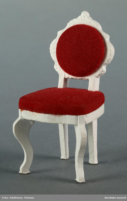 Möblemang med a) soffa och b-c) två stolar i bondrokoko tillverkad av vitmålat trä och rött sammetsliknande tyg. Fabrikstillverkad. Hör till inredningen i hallen på första våningen i dockskåp NM.0331721+. och är placerad längs långväggen, mittemot hallspegeln.