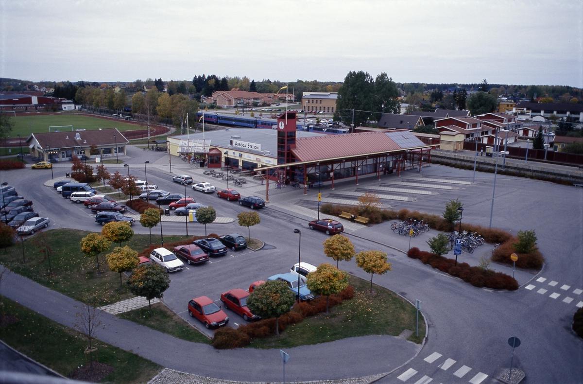 Arboga station vid Centrumleden. Resecentrum. Ett tåg kommer in på perrongen. Utanför järnvägsstationen ligger parkeringsplatser för bilar och hållplatser för bussar. Till vänster ses idrottsanläggningen Sturehallen och Sturevallen. På andra sidan järnvägen ligger äldreboendet Trädgården. Bakom de höga träden skymtar Högskolecentrum.