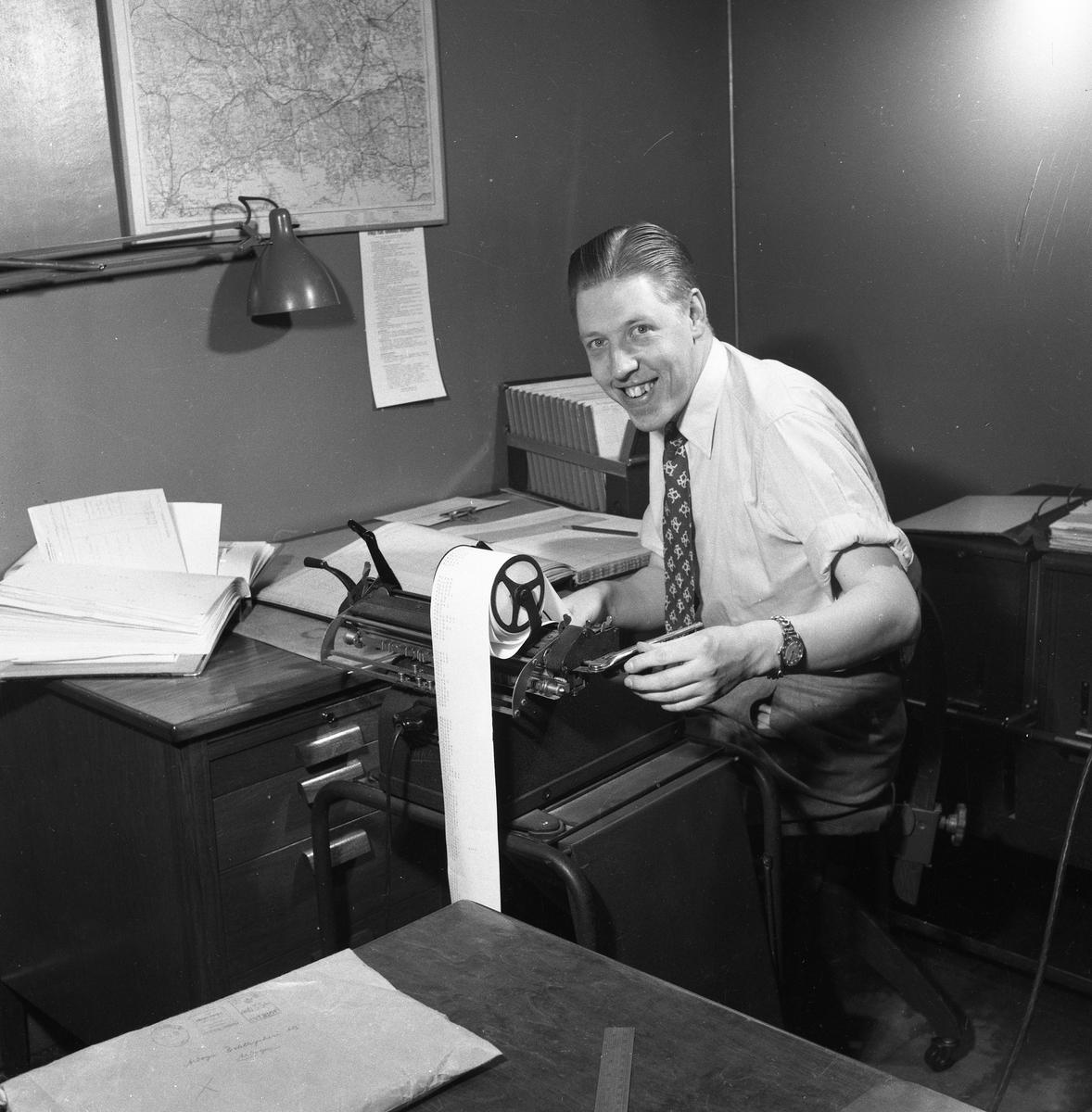Arboga Tidning, personal och interiör. En man, iklädd skjorta och slips, arbetar vid en räknemaskin. Kontorsstolen är försedd med hjul. På skrivbordet ligger en uppslagen pärm. På väggen hänger en karta.