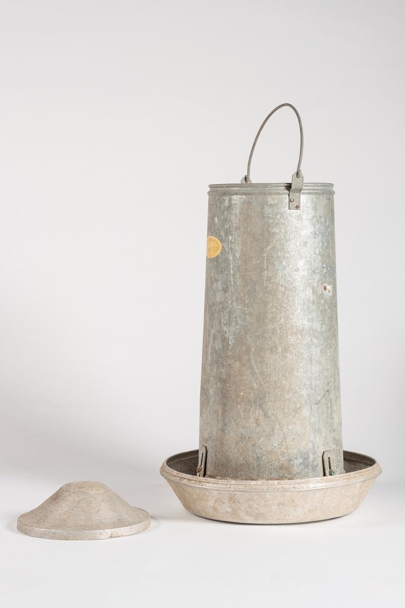 Sylinderformet beholder som står på tre ben i et rundt kar. Beholderen har lokk og åpning i bunn. Det er håndtak på beholderen som går over lokket.