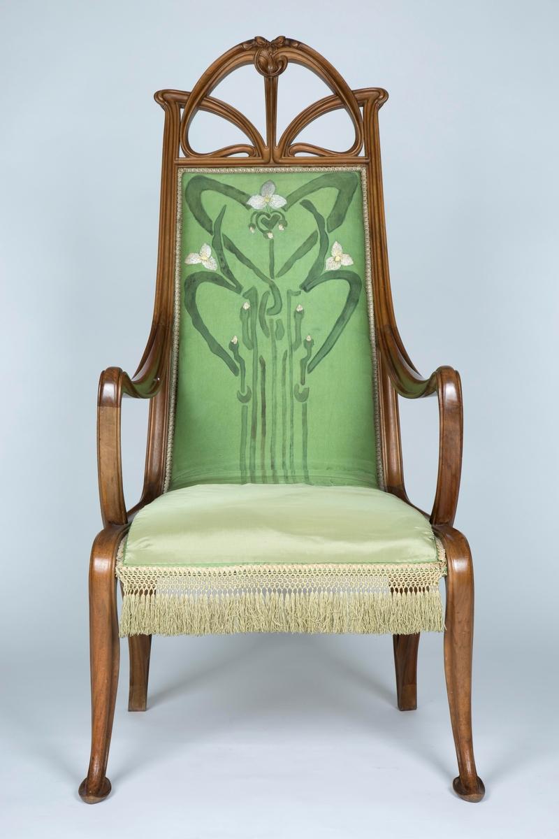 Lenestol i tre. Høyreist rygg som glir over i stolsetet. Treverket er utformet som slyngende plantestengler. Den organiske linjeføringen understrekes av at akterstavene glir over i bakbenene, og ryggen glir over i armlenene.   Toppstykket er dekorativt utformet som en symmetrisk komposisjon med tre orkidéblomster. Rygg og sete er stoppet, og trukket med et grønt silketrekk. Det er dels brodert, dels malt, med stiliserte orkidémotiver. Nedre del av trekket er dekorert med frynser.