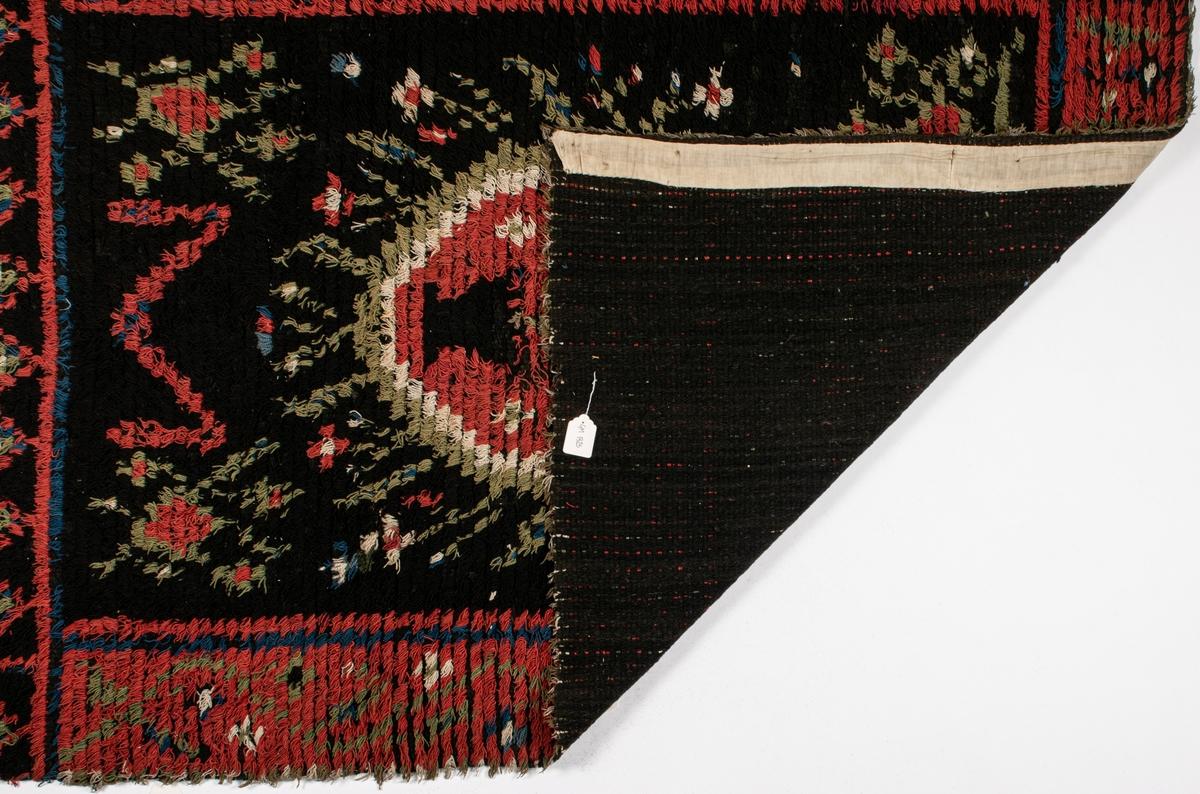 Rya, gjord i en våd, tämeligen gles. I mitten ett avrundat 8-kantigt fält med blomsterurna, korta grenar i radiärt från mittfältet, figurer i hörnen. Bårder, på långsidan röda med slingor, på kortsidorna svarta med rombiska figurer. Botten i övrigt svart med figurer i rött, ljusgrönt, blått och vitt.