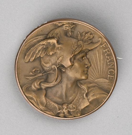 Motiv på forsiden er portrett av mannsperson med helm på hodet og på baksiden er det en kvinnefigur som holder i en ende av en rosenkrans som omgir en sirkelplate med påskrift og datering.