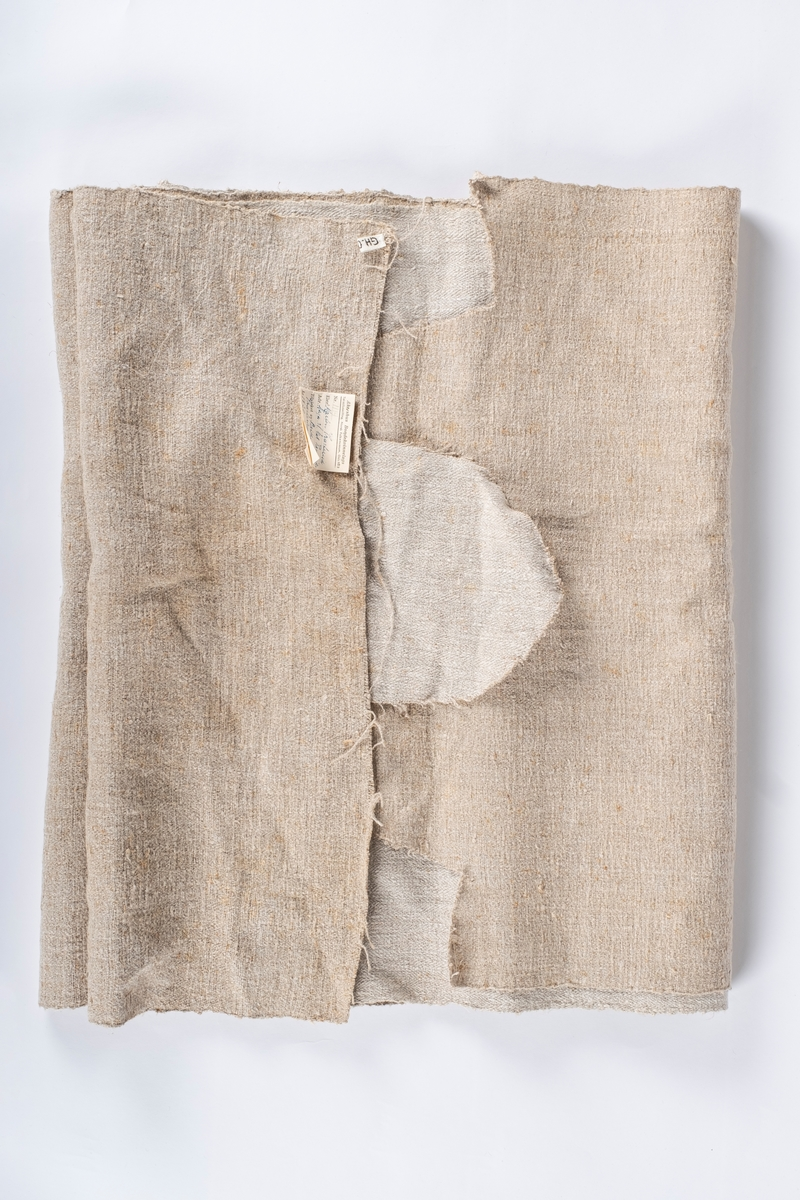 Grovt tekstil av naturlin. Deler av tekstilet er klippet av. Tekstilet er formet som et rektangel, men i den ene enden hvor deler av tekstilet er klippet av er det en flapp.