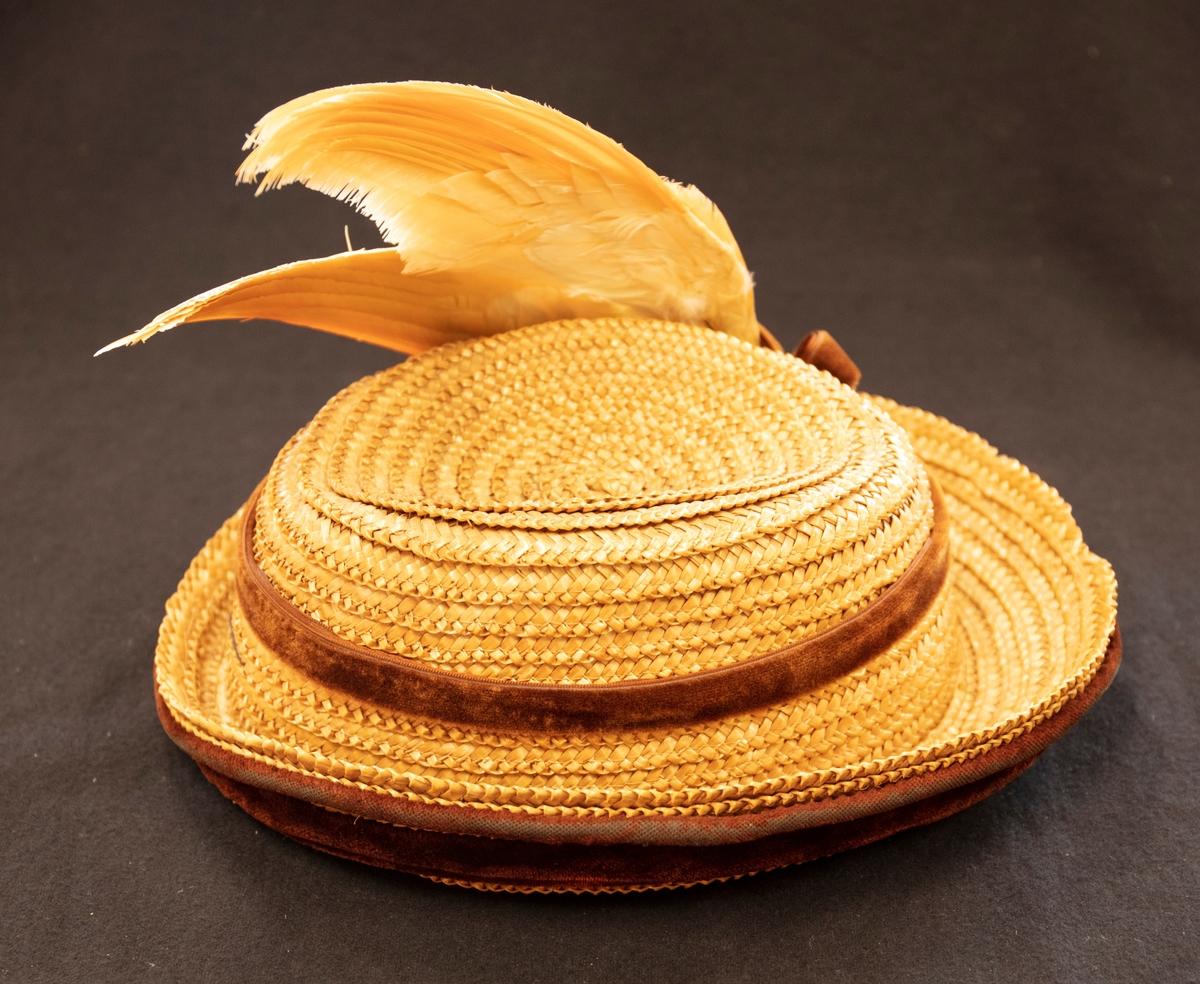 Halmhatt med brätte. Brättet är kantad med två band med brun sammet. På kullens övre kant finns ytterligare ett brunt sammetsband med rosett. Två orangetonade fågelvingar är fästa vid rosetten. Hatten är försedd med ett brunt gummiband.
