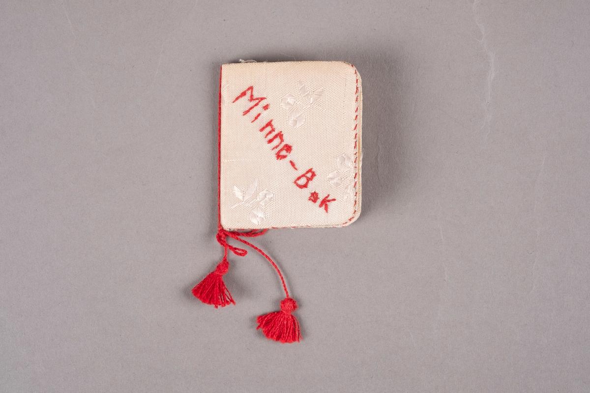 """En minnebok med omslag av papp kledd med tekstil med blomstermønster. En tråd med to dusker er knyttet rundt ryggen. """"Minne-Bok"""" er brodert på framsiden."""