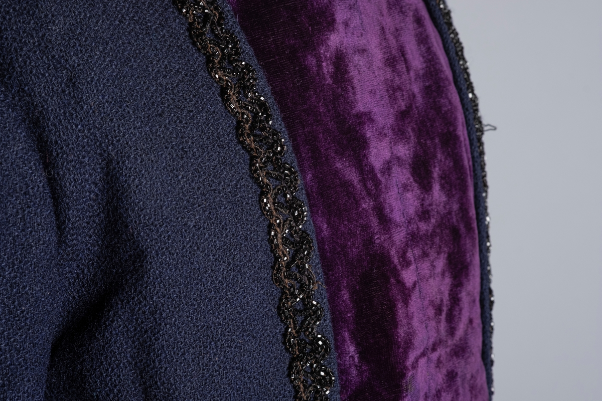 Todelt kjole med kjoleliv og skjørt. Blått kjoleliv, med hals og forstykke i lilla flløyel. Dekor av sort perlebroderi loddrett i hver side av fløyelen. Nederste kanten på  den ene perleraden kan ha blitt reparert, det er brukt annen tråd, og perler som er større og matte. Jakken er foret innvendig med lyst stoff. Foret hektes sammen i fremkant for lukking av livet, en klaff med lilla fløyel legges over og festes på undersiden av jakkeslaget. Ermene er foret med grått stoff, og fløyelen med sort stoff. Kjolelivet lukkes også med to hemper og hekter i siden på halsen. Kjolelivet festes til skjørtet med to hekter på fremsiden, og tre på baksiden. Innvendig har kjolelivet tre spiler, to i ryggen og en i jakkeslaget. Langt blått skjørt med lomme. Innvendig foret med sort stoff. I livet er det en hempe av sort stoff. Lukkes med to hekter og hemper i livet. Festet til kjolelivet med hemper. Nederst på skjørtet er det en forsterkningskant med en blå slitelist av bånd og floss.