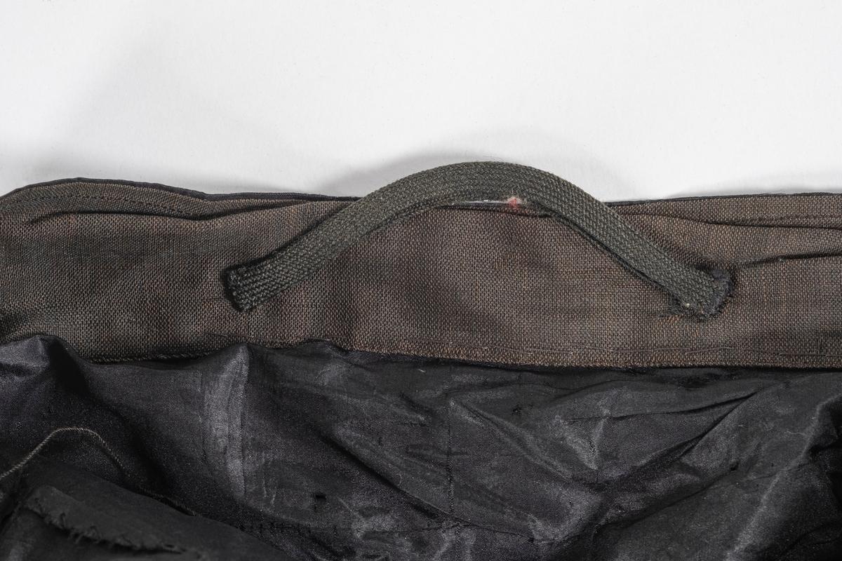 Sort skjørt av taft med håndsydd lomme av bomullstoff i siden. . To små metallhekter og metallhemper i livet, med rynker i livet under hempene. bomullstoff i livet og i nedre kant av skjørtet. Hempe av mørkegrønt stoff i livet.