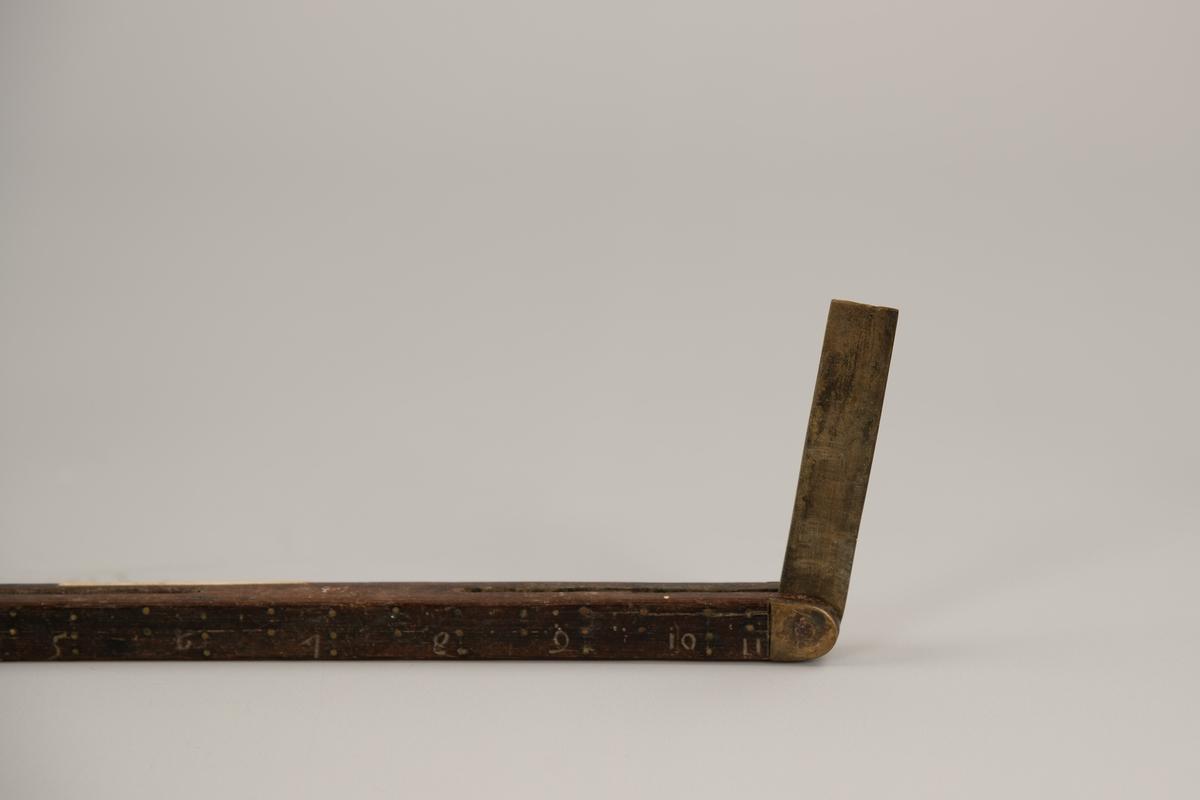 Tommestokk som er merket O. T. S. B.  I hver ende ligger en messingstang som kan skyves ut og  forlenger tommestokken.