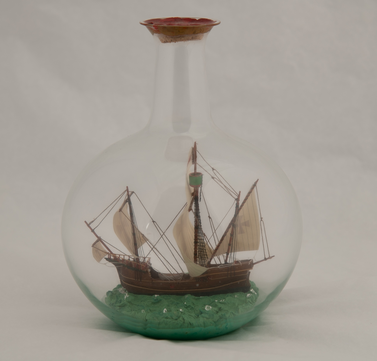 """Flaskeskute i kuleformet flaske. Skuta er: """"Santa Maria"""" , 1492 , en karakk , som var flaggskipet til Columbus.  Brunt skrog med lyse striper , seil med malteserkors i rødt."""