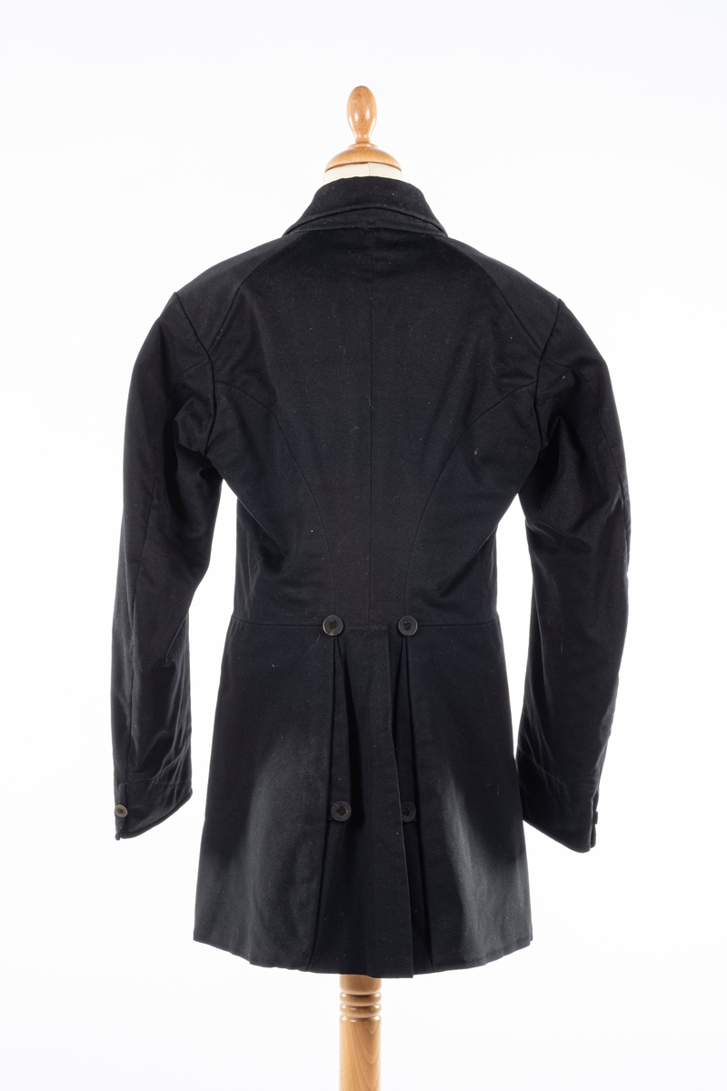 Dobbelt spent frakk som kneppes med fire knapper på hver side. De øverste kan ikke kneppes. Knappene er kledd med silke med fløyelsornament i midten. Hempe i nakkelinning. Det er splitt med legg fra livet og ned, med en knapp over splitten på hver side. Det er også to knapper lenger ned i splitten, og en knapp på hver mansjett. Frakken er foret.