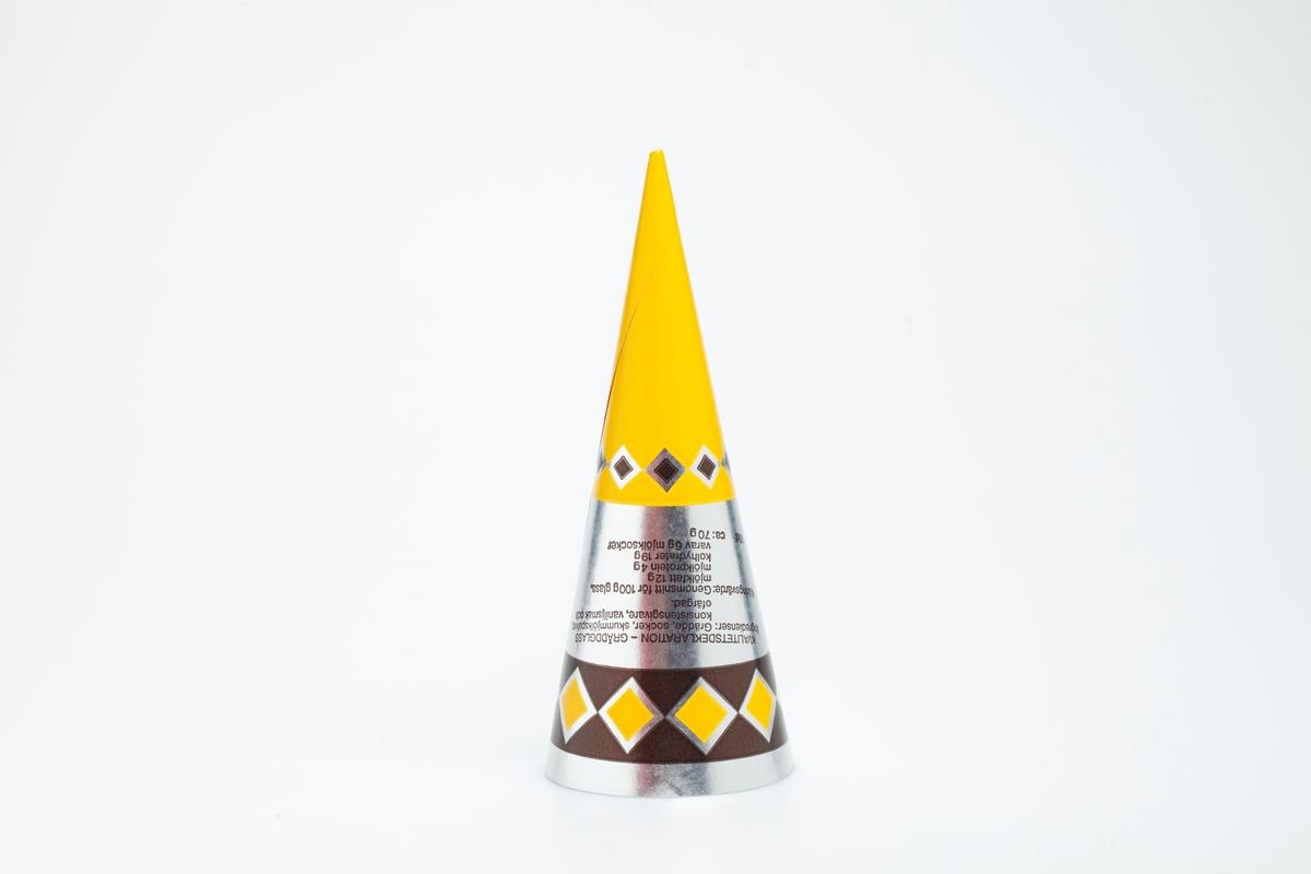 Kjegleformet iskrempapir (kremmerhus) i aluminium. Kremmerhuset er blankt med farger på utsiden, og matt uten farge (hvit) på innsiden. Kremmerhuset er gult i nedre halvdel og sølvfarget i øvre halvdel. En brun bord øverst, med en rekke kvadrater stående på et hjørne. Det er også en slik rekke øverst i det gule området. En rund logo bryter det brune båndet i øvre del.