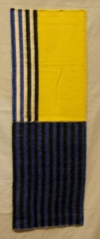 Vävprov till filt vävd i korskypert med inslagseffekt hopsydd på mitten i mjuk och tjock kvalitet. Det är ullgarn, filtgarn 6/2, i både varp och inslag. Varpen är enfärgad vit och inslaget är svart, blått, gult och vitt. Vävprovet är randigt i svart och blått på den ena halvan. På den andra halvan är det ett enfärgat gult parti och två svarta och två blå ränder på vit botten. Filten är ej vändbar då varpeffekten på avigsidan ger gryniga färger.  Långsidorna är vikta och sydda med langettsöm med svart, gul och blå tråd på respektive ruta. Vävprovet är märkt med R27:2 på ett vitt band.  Se även inv.nr 0027:1 Filt Afrika  Vävprov till filt med modellnamn Afrika är formgivet av Ann-Mari Nilsson och tillverkat av Länshemslöjden Skaraborg. Det finns med  på sidan 64-65 i vävboken Inredningsvävar av Ann-Mari Nilsson i samarbete med Länshemslöjden Skaraborg från 1987, ICA Bokförlag. Se även inv.nr. 0001-0026,0028-0040.