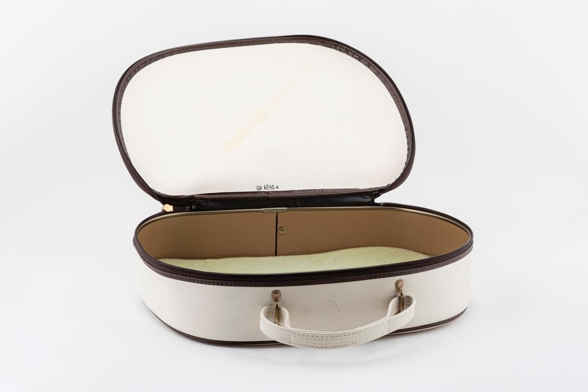 Koffert for oppbevaring av hårføner. Kofferten er oval med håndtak og lukkes med glidelås. Den av imitert skinn i hvit med brune kanter. På innsiden er det skumgummi i bunn.