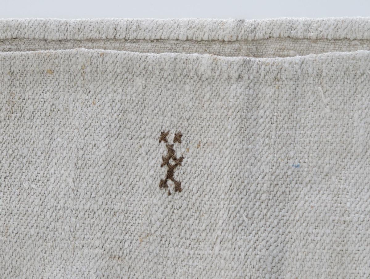 Melsekk av tettvevd lerretsduk. Av to stykker tøy, håndsøm langs bunnen og langsidene . Materialet er usikkert, men antakelig bomull (kanskje lin ? ) Sekken har  påsydd snor rundt åpningen. Merket med broderte bokstaver XX i sort farge.