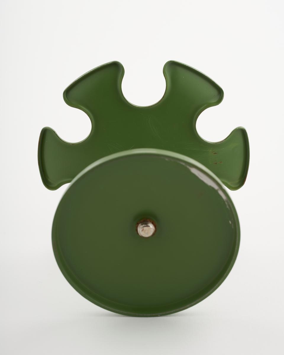 Grønn stempelholder med plass til å henge seks stempler. Den øverste runde delen er til å henge stempler på. Den nederste runde delen er en fot. Den øverste og den nederste runde delen er forbundet med en stang.  NAV-samlingen er en gruppe av gjenstander som har vært anvendt på sosialkontoret (Aetat - NAV) i Skedsmo kommune.