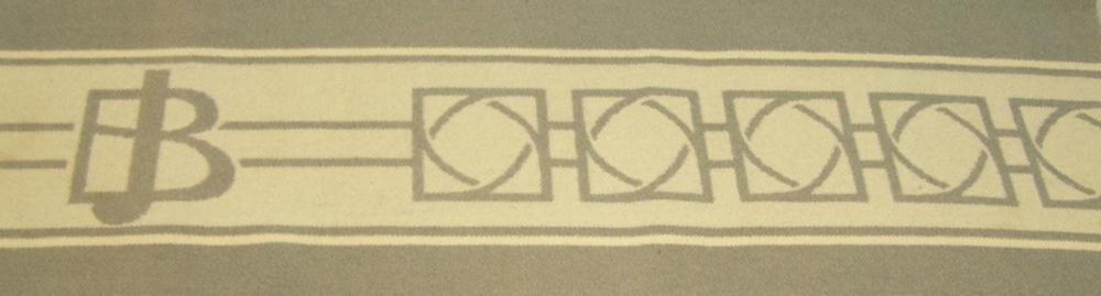Rektangulär filt av ylle. I ljust grågrön färg, något blekt i färgen. Bård upptill och nedtill i abstarkt mönster och bokstäverna BJ. Bården är i vitt mot den grågröna bottnen, på filtens avigsida är mönstret spegelvänt och färgerna omkastade. Sydd med kaststygn utmed kortsidorna.