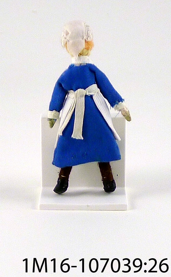 Docka, med blå klänning med vita glaspärlor som knappar, vit krage och vita manschetter, vitt förkläde, vit mössa, rosa underbyxor. Ljust hår av ullgarn. Benen är virade med brunt ullgarn, svarta skor. Målat ansikte på tyg. Tillverkad av Anna Rönne.
