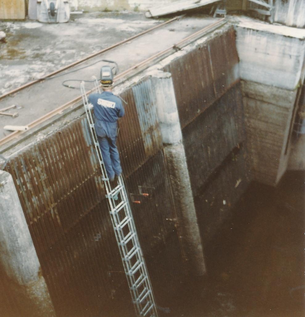 Mann står på stige og holder på med reparasjoner av varegrind på Kistefoss
