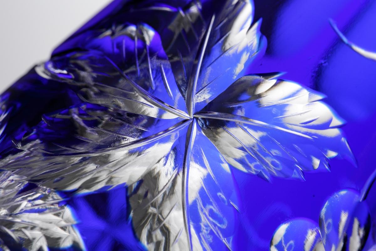 Karaff med blått överfång. Slipad dekor med vinrankor samt facettslipade partier.