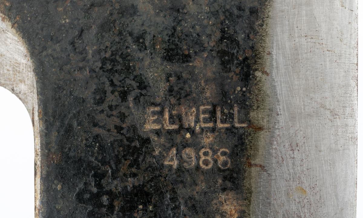 Barkespade, muligens også med kvistingsfunksjon, fra en produsent som etter et stempel på blad og skaft å dømme kalte seg «Elwell» (jfr. fanen «Historikk»). Bladet er er L-formet, lagd av ei 5 millimeter tjukk stålplate, der det i den fremre enden har en aning konvekst buet, rettstilt egg som er cirka 11,6 centimeter lang (opprinneligvi sannsynligvis cirka 1 centimeter lengre, det er slått av et skår i det ene hjørnet).  På dette barkespadebladet er også to av de andre sidekantene skarpslipt på samme måte, muligens med henblikk på at redskapet også skulle kunne brukes til å fjerne småkvist i hoggende eller nappende bevegelser. I forlengelsen av det 17 centimeter lange bladet er det smidd en kon fal (skaftholk) med gjennombrutte hull for en maskinskrue som forankrer bladet i et treskaft. Den øvre delen av bladet er svartlakkert mens eggpartiene og falen er stålblanke, falen riktignok med en del rustflekker. Redskapet har et runddreid 91 centimeter langt skaft av et hardt treslag.  Redskapet har en totallengde på 108 centimeter. Denne barkespaden veier 1470 gram.