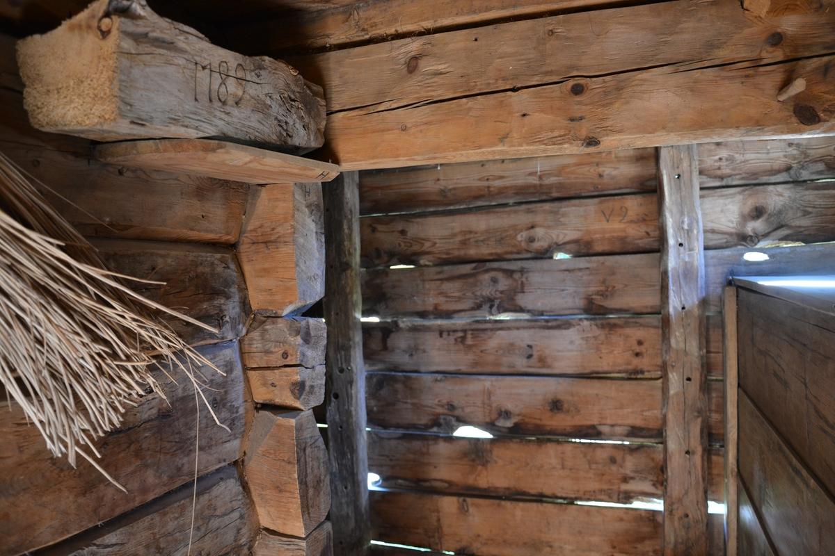 """Tømra stabbursrom med skot på kvar side i reisverk med kledning. Også """"døra"""" (fram-rommet) er av reisverk med kledning.  I andre høgda er det tømra heilt ut i begge endene, også over """"gangen"""". Vindauge i kvar gavl.   Veggane i skota skrånar ut oppe. Glas i sjølve stabbursrommet og i begge gavlane i andre høgda,, og i skota. Trenaglar i kledning og golvbord. Trenabbar på veggane inne i andre høgda, til å henge ting på.  Ved riving fann ein ei knust glasrute med glasmåleri, eit bilde med namn.  Bygningen har ikkje spor etter noko ombygging.  Original kledning med trenaglar. Det har vore brukt klypt spikar og, truleg """"forsterking"""" som har vore gjort seinare.  I gangen er det trapp opp til lemmen, til venstre for døra, og går opp igjennom ei luke.  Til høgre for døra er korn-byra. Under denne låg det tynne steinheller då stabburet vart flytta. . Vindauget har små blyinnfatta ruter - mange av dei er opphavelege, men nokre sekundere, og blyråmene er """"nye"""" (uvisst kva def.) På innsida av glaset er det ei luke med kraftige hengsler og lås. Hengslene er laga slik at ein ikkje kan løfte luka av. Det går trapp opp på lemmen både frå gangen og hovudrommet i første høgda. I andre høgda er det to rom, eit i kvar ende, og kvar av trappene går opp til kvart sitt rom. heile andre høgda er tømra."""